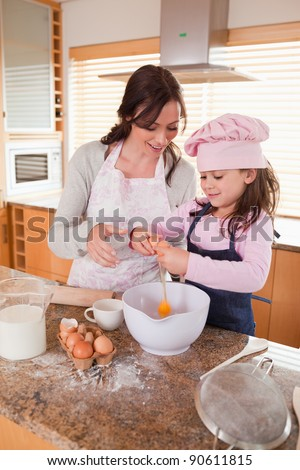 Portrait of a mother and her happy daughter baking in a kitchen - stock photo