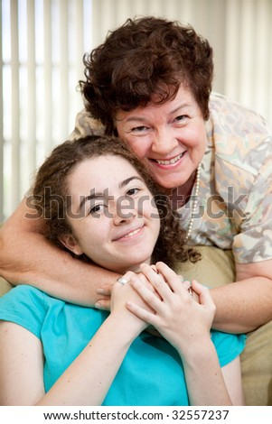Portrait of a mother giving her teen daughter a big hug. - stock photo