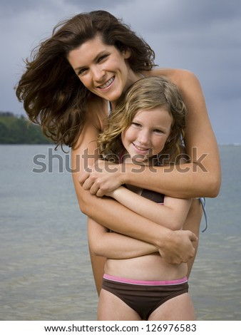 Portrait of a mother hugging her daughter - stock photo
