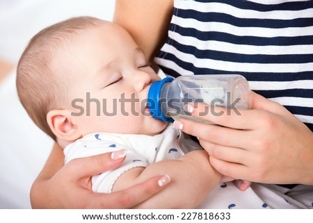 Portrait of a mother is  feeding her little baby boy from the milk bottle. - stock photo