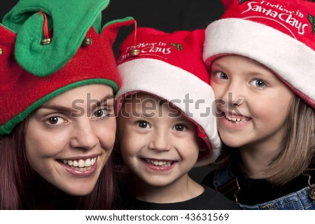 Portrait of a mother, son and daughter dressed in Christmas hats - stock photo