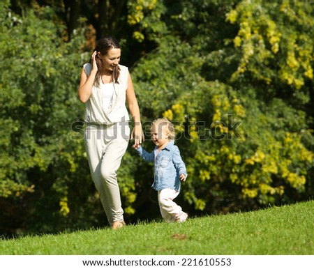 Portrait of a mother walking outdoors with baby - stock photo