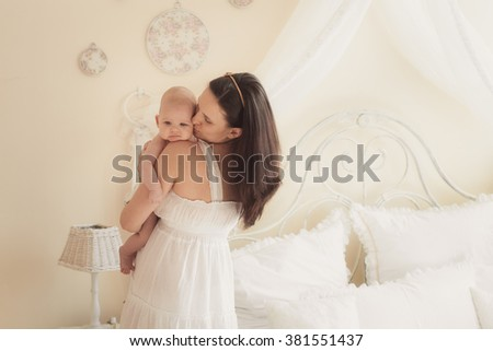 Portrait of a mother with a newborn in a light room - stock photo