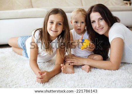 Portrait of a mother with her baby and pre-teen children having fun on white carpet in living room at house - stock photo