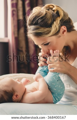 Portrait of a mother with her 4 months old baby at home. Happy child near to mum in her room. Portrait of a mother with her newborn baby. - stock photo