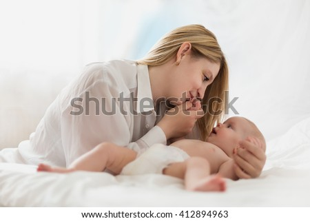 Portrait of a mother with her newborn baby in white bedroom - stock photo