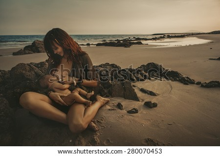 Portrait of a mother with Newborn Baby in the beach  - stock photo