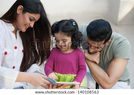 portrait of a multi ethnic family in outdoor, mother and reading a story for her little daughter. - stock photo