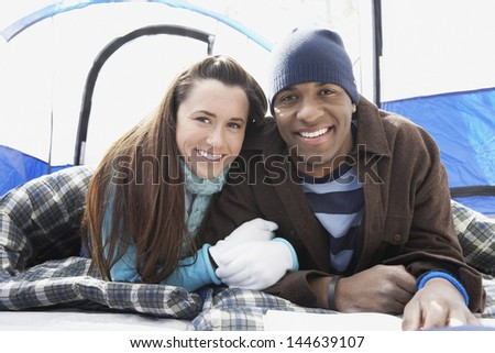 Portrait of a multiethnic young couple lying in sleeping bags in the tent - stock photo