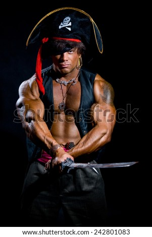 Portrait of a muscular man in a pirate costume. Aggressive man with a sword on a black background - stock photo