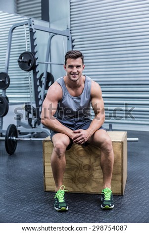 Portrait of a muscular man sitting on a wooden box - stock photo