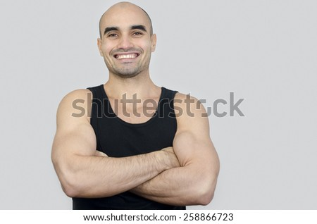 Portrait of a muscular man smiling. Handsome bald man with arms crossed. Happy fit athletic man in black tank top. - stock photo