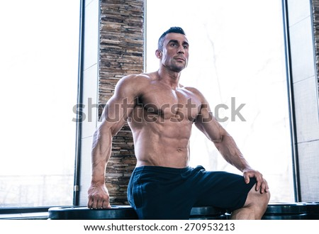 Portrait of a muscular pensive man resting at gym - stock photo