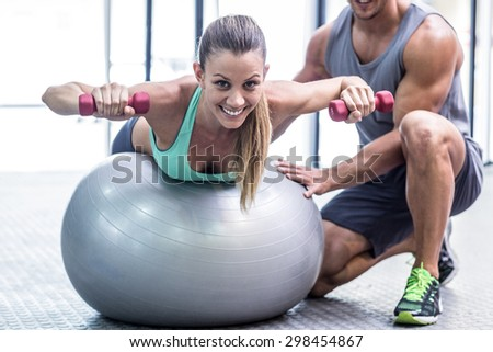 Portrait of a muscular woman balancing while lifting dumbbells - stock photo
