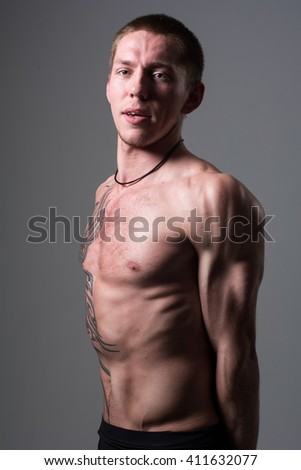 Portrait of a muscular young man. Sports trained man on a gray background - stock photo