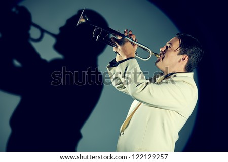 Portrait of a musician playing the trumpet at studio. - stock photo