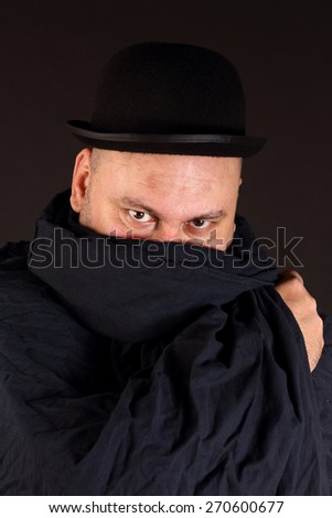 Portrait of a mysterious man with bowler hat - stock photo