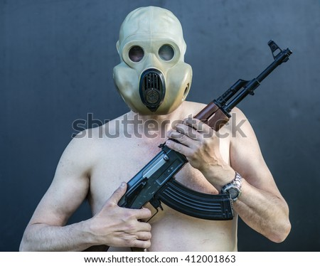 portrait of a naked man in a gas mask with a gun - stock photo