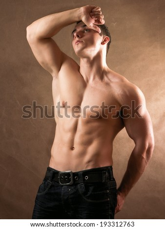 Portrait of a naked muscular man, isolated on beige background - stock photo