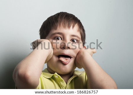 portrait of a naughty boy, teasing you with a chewing gum in a mouth, concept of misbehave - stock photo
