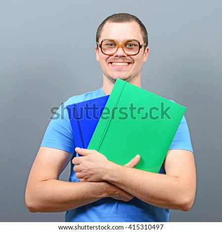 Portrait of a nerd holding books with retro glasses - stock photo