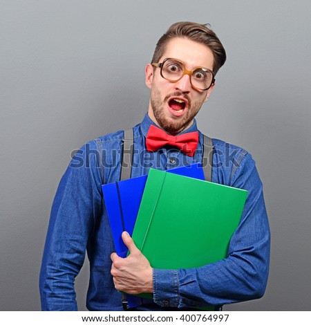 Portrait of a nerd holding books with retro glasses against gray background - stock photo