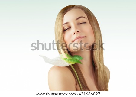 Portrait of a nice blond girl with closed eyes enjoying day spa, holding beautiful fresh calla flower, beauty treatment and alternative medicine - stock photo