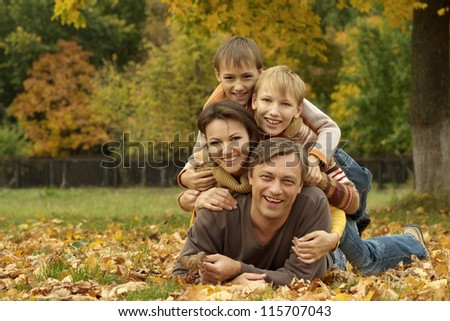 portrait of a nice happy family lying in autumn park - stock photo