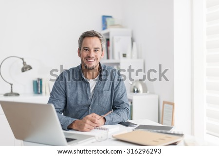 Portrait of a nice smiling grey hair man with beard, working at home on some project, he is sitting at a white table looking at camera, writing ideas with his laptop in front of him. Focus on the man - stock photo