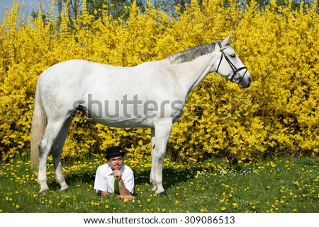Portrait of a nice white horse and young man on spring background - stock photo