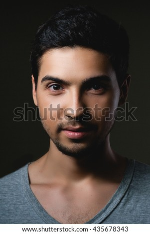 Portrait of a normal boy  over grey background / Attractive young man in studio looking at camera - stock photo