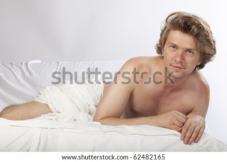 Portrait of a nude man relaxing in bed. Studio image. See more in my portfolio - stock photo