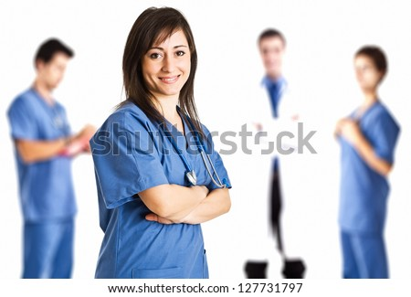 Portrait of a nurse in front of her medical team - stock photo