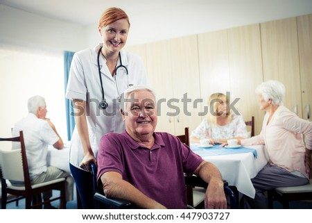 Portrait of a nurse with senior man in wheelchair in the retirement house - stock photo