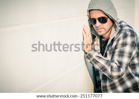 Portrait of a one sad man in sunglasses sitting outdoors near the house at the day time - stock photo