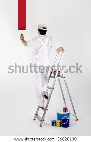 Portrait of a painter painting a white wall in red - stock photo