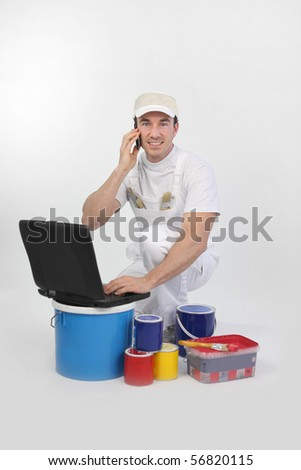Portrait of a painter sitting in front of a laptop computer with a mobile phone - stock photo