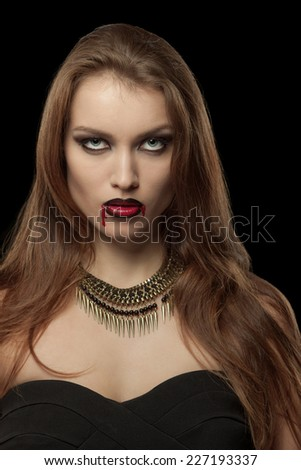Portrait of a pale gothic vampire woman on a black background - stock photo