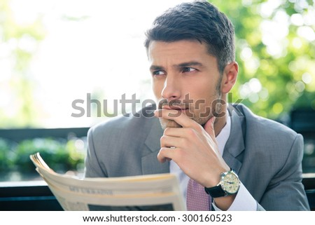 Portrait of a pensive businessman holding newspaper and looking away outdoors - stock photo