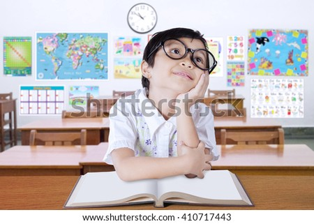Portrait of a pensive elementary school student sitting in the classroom with a book on desk and wearing glasses - stock photo