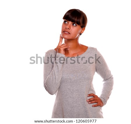Portrait of a pensive hispanic young woman looking up on grey dress - copyspace - stock photo