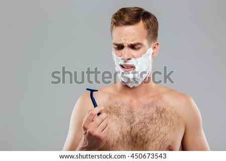 Portrait of a pensive man before shaving over gray background - stock photo