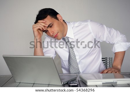 Portrait of a pensive man in suit in front of a laptop computer - stock photo