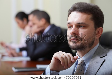 Portrait of a pensive mature businessman in suit with his team working behind - stock photo