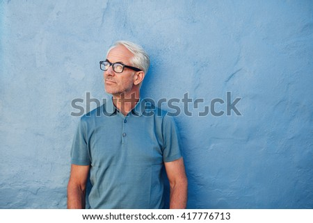 Portrait of a pensive mature man standing against a blue wall and looking away. Caucasian mid adult male with glasses. - stock photo