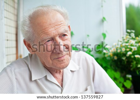 portrait of a pensive senior man looking into the distance - stock photo