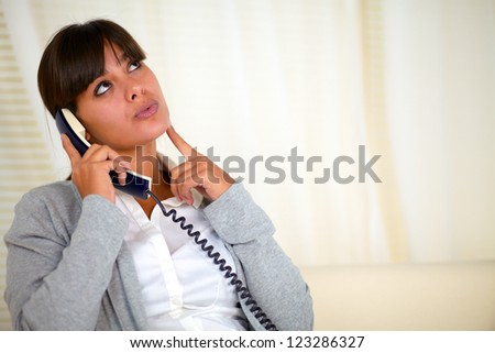 Portrait of a pensive woman looking up while speaking on phone - copyspace - stock photo
