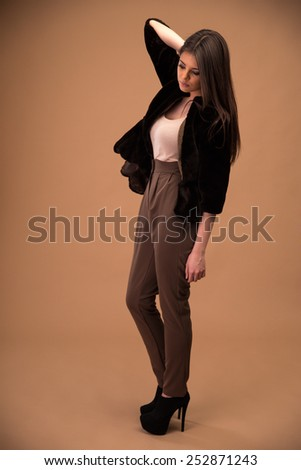Portrait of a pensive young fashion woman over brown background - stock photo