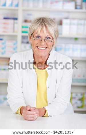 Portrait of a pharmacist in the pharmacy leaning on the desk - stock photo