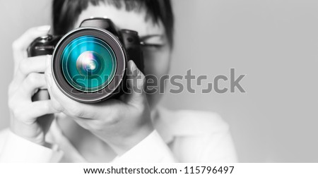 Portrait of a photographer covering her face with the camera - stock photo